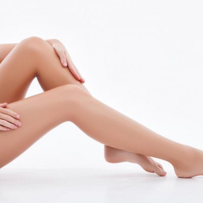 Close up of female feet. The woman is touching her smooth legs with gentleness. Isolated